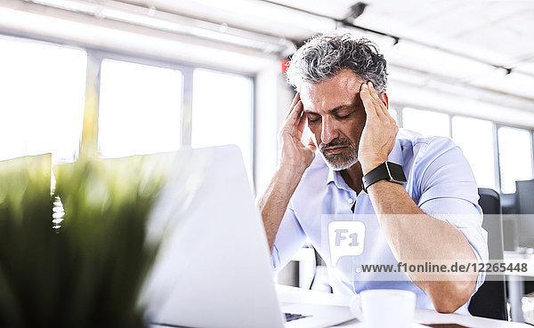 Gestresster reifer Geschäftsmann am Schreibtisch im Büro mit Laptop