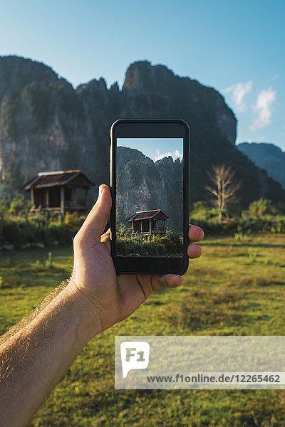Laos,  Handheld Smartphone,  Display mit Holzhütte und Bergen