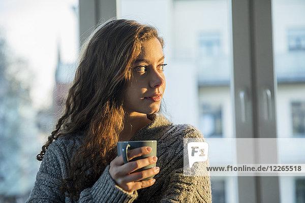 Porträt eines jungen Mädchens mit Kaffeetasse,  die abends aus dem Fenster schaut.