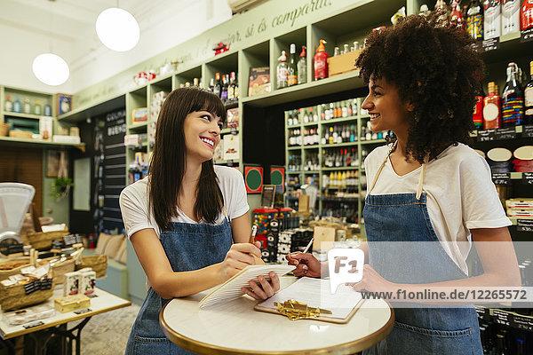 Zwei lächelnde Frauen in einem Laden  die sich Notizen machen.