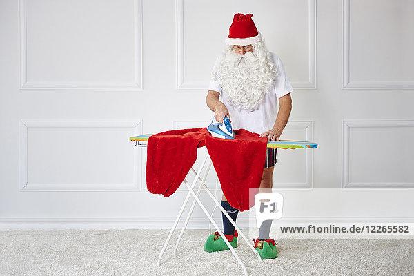Der Weihnachtsmann bügelt sich die Hosen.