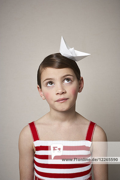 Portrait of little girl with paper boat on her head