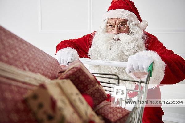 Porträt des Weihnachtsmannes mit Einkaufswagen von Weihnachtsgeschenken