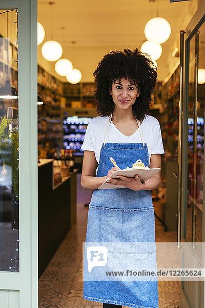 Porträt einer lächelnden Frau mit Zwischenablage in der Eingangstür eines Ladens