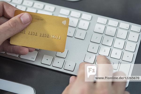 Mann bei der Online-Zahlung mit Kreditkarte am Schreibtisch  Nahaufnahme