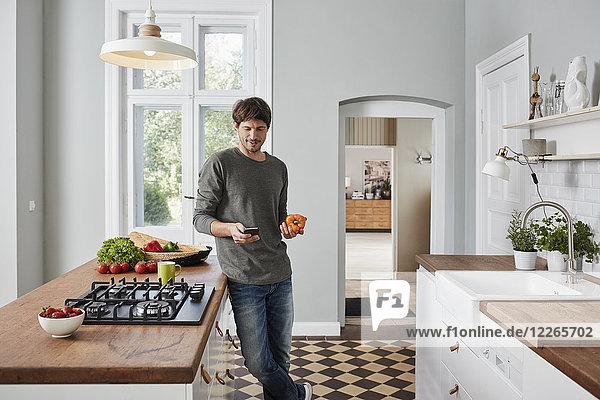 Mann mit Smartphone und Paprika in der Küche