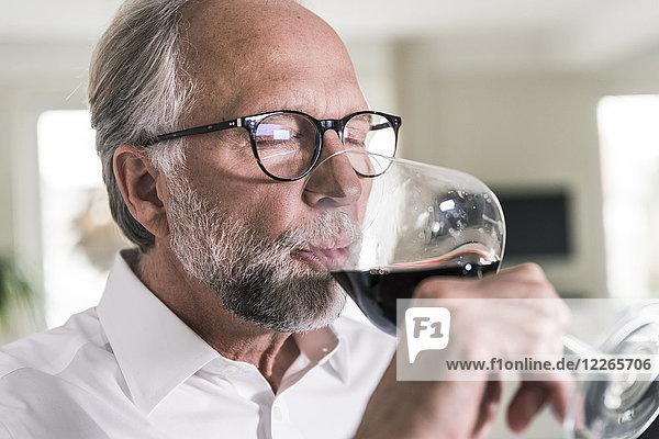 Porträt eines reifen Mannes  der ein Glas Rotwein trinkt.