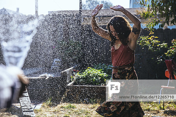 Wasser spritzt auf junge Frau im Hinterhof