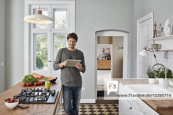 Lächelnder Mann mit Tablette in der Küche