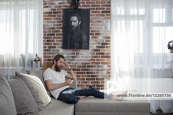 Mann mit Handy entspannt auf der Couch zu Hause