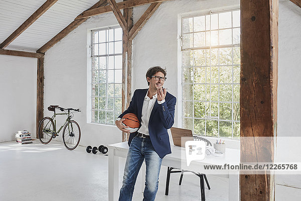 Geschäftsmann mit Basketball mit Smartphone im Penthouse