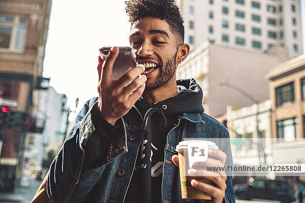 Porträt eines stilvollen jungen Mannes mit Kaffee und Smartphone auf der Straße