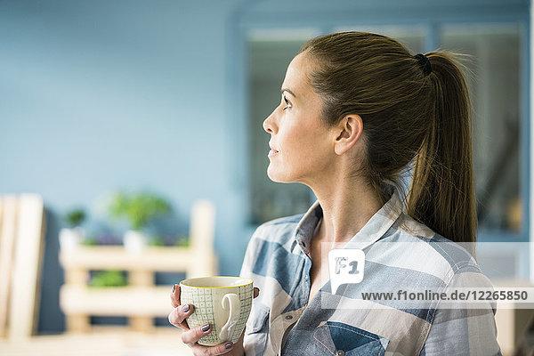 Woman refurbishing her new home  taking a break  drinking coffee