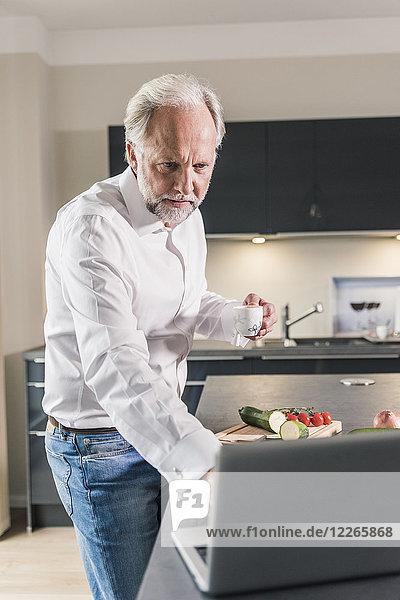 Portrait eines reifen Mannes mit Laptop in der Küche