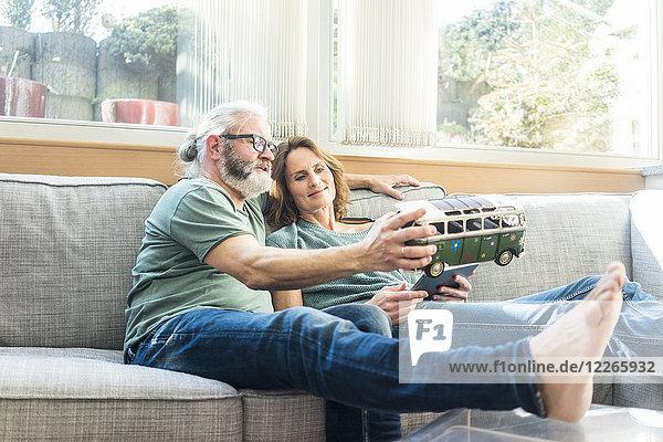 Erwachsenes Paar auf der Couch zu Hause mit Kleinbusmodell