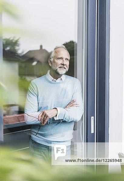 Erwachsener Mann mit Blick aus der Terrassentür