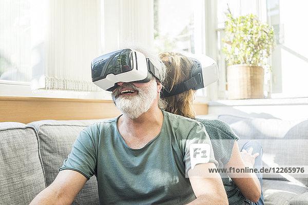 Glückliches reifes Paar  das zu Hause auf der Couch sitzt und eine VR-Brille trägt.