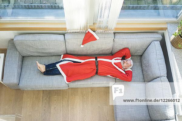 Bärtiger reifer Mann im Weihnachtsmann-Kostüm auf der Couch im Wohnzimmer liegend