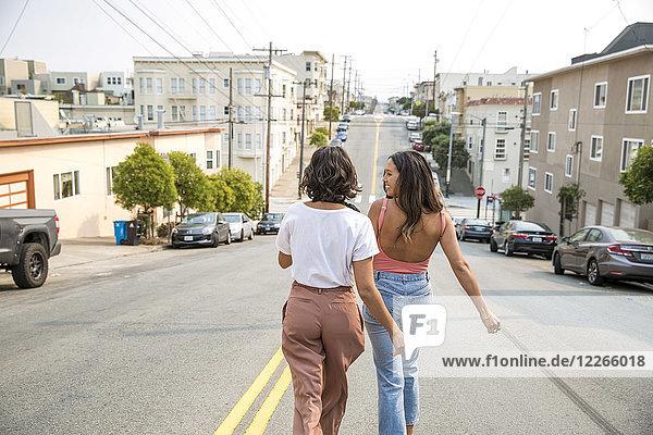 Zwei junge Frauen  die die Straße entlang gehen.