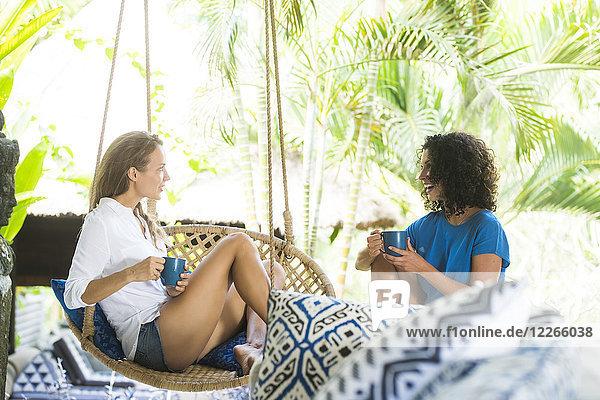 Zwei Frauen reden auf der Terrasse bei einer Tasse Kaffee.