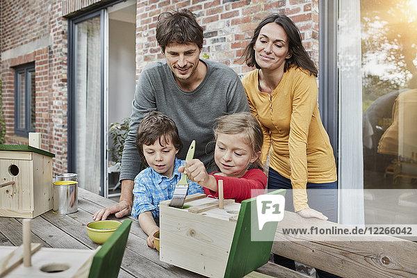 Familie bei der Arbeit am Vogelhaus vor dem Haus