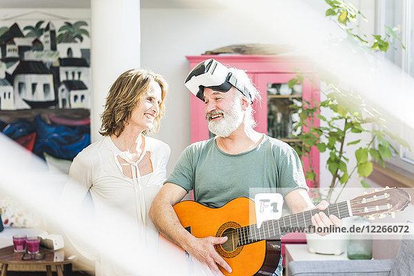 Ein glückliches reifes Paar mit einem Mann  der Gitarre spielt und eine VR-Brille trägt.