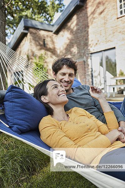 Happy couple lying in hammock in garden of their home