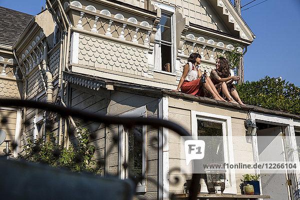 Zwei junge Frauen sitzen auf dem Dach