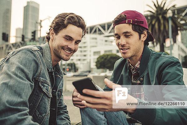 Zwei lächelnde junge Männer teilen sich ihr Handy im Freien.