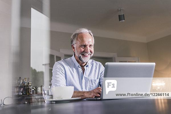 Porträt eines glücklichen reifen Mannes  der zu Hause am Tisch sitzt und einen Laptop benutzt.