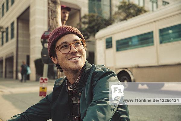 Porträt eines stilvollen jungen Mannes  der auf dem Bürgersteig sitzt