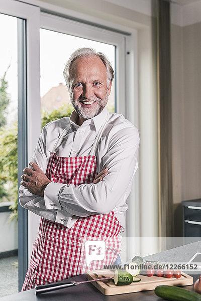 Porträt eines lächelnden reifen Mannes mit Schürze in der Küche