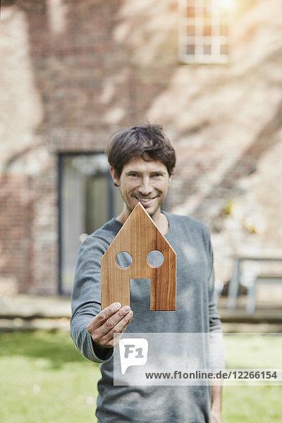 Porträt eines lächelnden Mannes vor seinem Haushaltenden Hausmodell