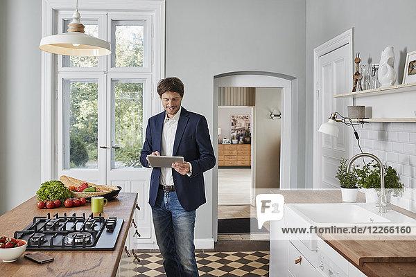 Mann mit Tablette in der Küche