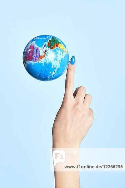 Nahaufnahme des Globus neben dem Finger der Frau