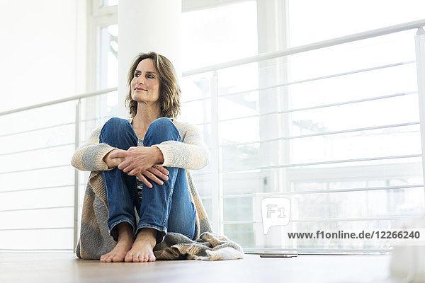 Entspannte Frau zu Hause auf dem Boden sitzend