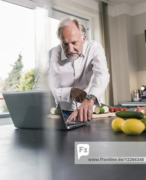 Der reife Mann bereitet das Essen in der Küche zu  während er den Laptop benutzt.
