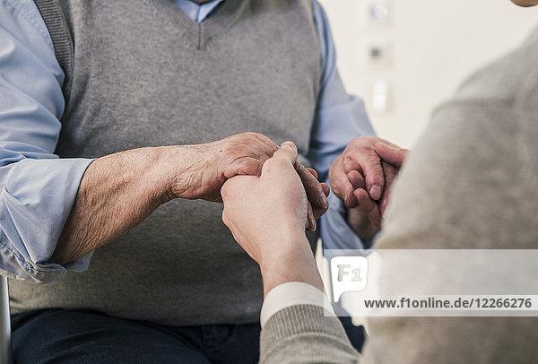Nahaufnahme eines älteren Mannes und eines jungen Mannes  der Händchen hält.