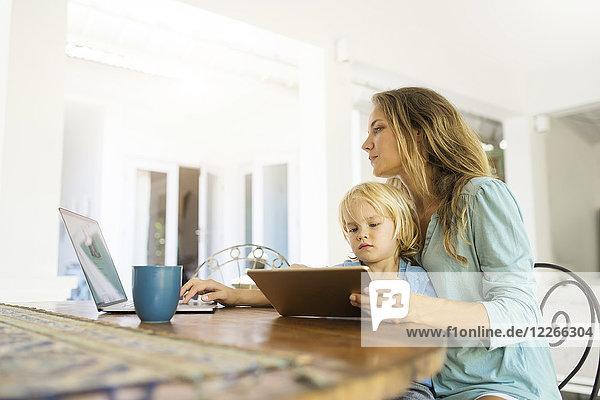 Junge sitzt auf dem Schoß seiner Mutter und schaut auf eine Tafel  während seine Mutter an einem Laptop arbeitet.
