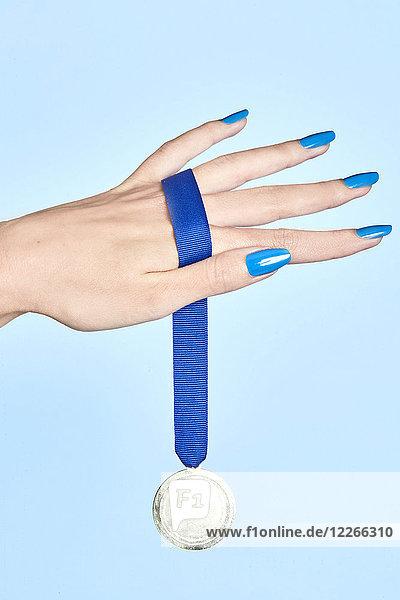 Nahaufnahme der Frauenhand mit einer Medaille