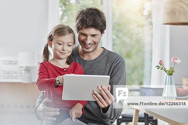 Lächelnder Vater und Tochter mit Tablette zu Hause zusammen