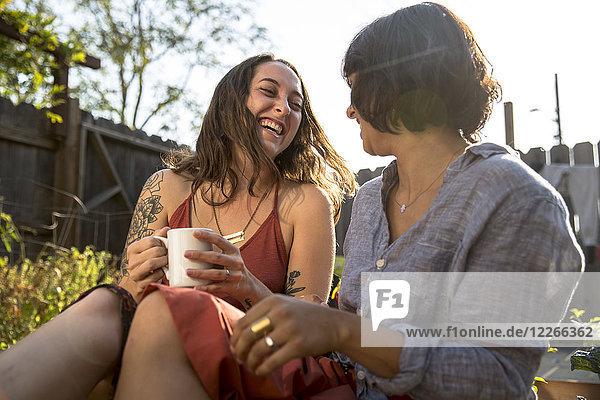 Zwei glückliche junge Frauen  die im Hinterhof reden.