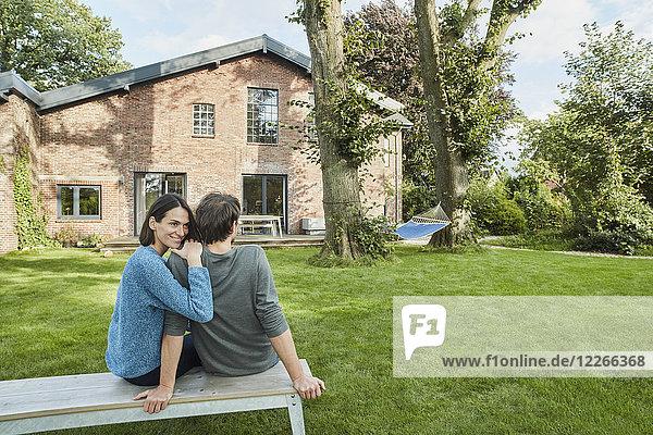 Lächelndes  liebevolles Paar  das im Garten seines Hauses sitzt.
