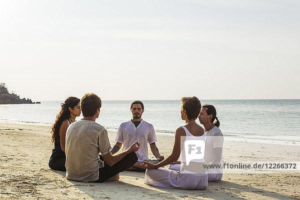 Thailand  Koh Phangan  Gruppe von Menschen  die gemeinsam an einem Strand meditieren.
