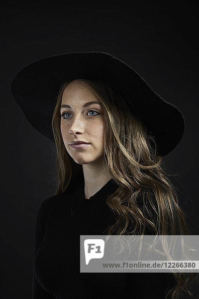 Porträt einer jungen Frau mit schwarzem Hut und Kleidung vor schwarzem Hintergrund