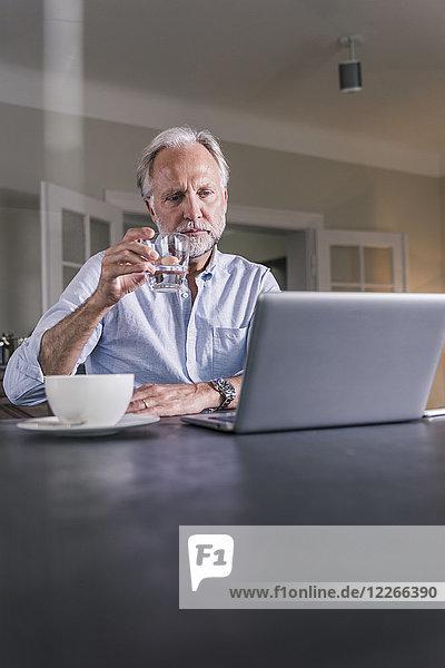 Nachdenklicher reifer Mann sitzt am Tisch mit einem Glas Wasser und schaut auf den Laptop.