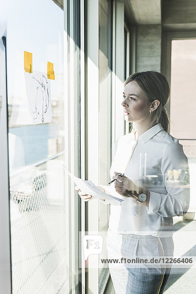 Young businesswoman looking at paper at the window