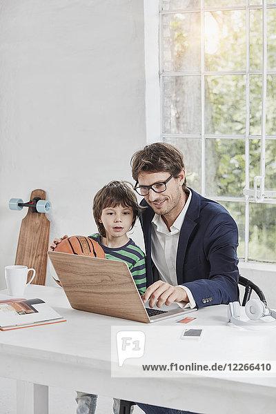 Geschäftsmann und Sohn mit Laptop am Schreibtisch