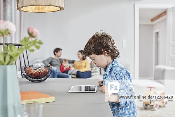 Junge schaut zu Hause mit Familie im Hintergrund auf die Tablette
