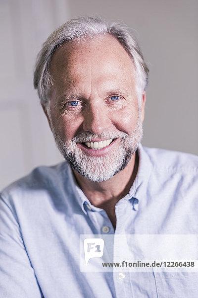 Porträt eines lachenden reifen Mannes mit blauen Augen und grauen Haaren